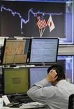 Трейдер следит за ходом торгов на бирже в Токио, 25 марта 2011 года. Фондовые рынки Азии завершили торги разнонаправленно: Япония и Китай выросли, а Южная Корея и Гонконг снизились.  REUTERS/Toru Hanai