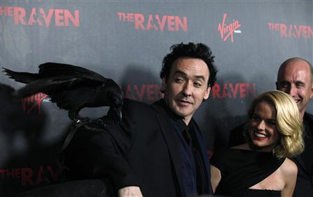 Cast member John Cusack poses with a raven named Suge, as co-star Alice Eve and director of the movie James McTeigue watch, at the premiere of ''The Raven'' at the Los Angeles theatre in Los Angeles, California April 23, 2012. The film opens in the U.S. on April 27. REUTERS/Mario Anzuoni