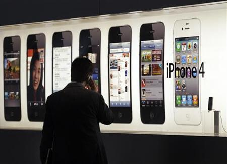 A man talks on an iPhone in front of an advertisement displayed at Hong Kong's first Apple Store at Two IFC before its opening in the financial Central district in this September 21, 2011 file photo. REUTERS/Tyrone Siu/Files