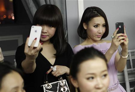 Guests take pictures of themselves with their iPhones during a fashion show by designer Bill Gaytten as part of his Spring/Summer 2012 collection for French fashion house Dior in Shanghai April 14, 2012. REUTERS/Stringer