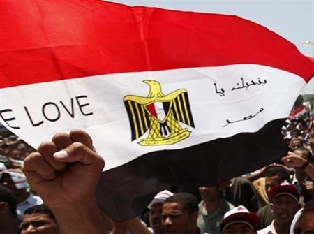 A protester raises his fist next to the Egyptian flag with the words, ''We Love Egypt'' as he shouts slogans against the government and military rulers after Friday prayers at Tahrir square in Cairo July 22, 2011. REUTERS/Mohamed Abd El-Ghany/Files