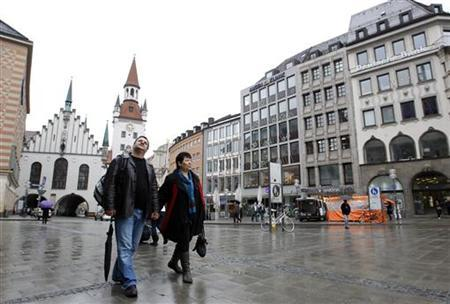 Greek hairdresser Maria Zatse (R) and her husband Niko walk across Marienplatz square in Munich March 19, 2012. REUTERS/Michaela Rehle/Files
