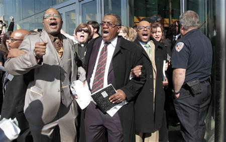 A group of Detroit pastors, including Homer Jamison (2nd R) and William Rideout (L), are escorted out of the Renaissance Center after disrupting General Electric Co's annual shareholders meeting being held in Detroit, Michigan April 25, 2012. REUTERS-Rebecca Cook