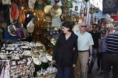 Tourists look at displayed items for sale as they tour in the medina, the old city of Tunis April 21, 2012. REUTERS/Zoubeir Souissi