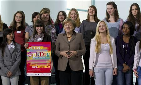 German Chancellor Angela Merkel (C) and pupils pose for pictures at the Girls Day career event at the Chancellery in Berlin April 25, 2012. REUTERS/Thomas Peter