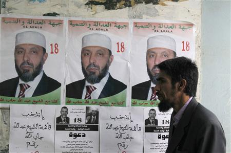 A man walks past an electoral poster of Sheikh Abdallah Djaballah, head of Front for Justice and Development party during a parliamentary election campaign rally in Medea, some 100 km (62 miles) west of the capital Algiers April 22, 2012. REUTERS/Louafi Larbi