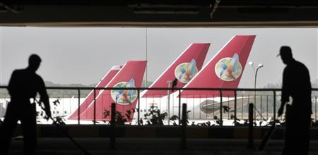 Airport staff is silhouetted as Kingfisher Airlines' aircrafts are seen parked at an airport in New Delhi April 12, 2012. REUTERS/Parivartan Sharma