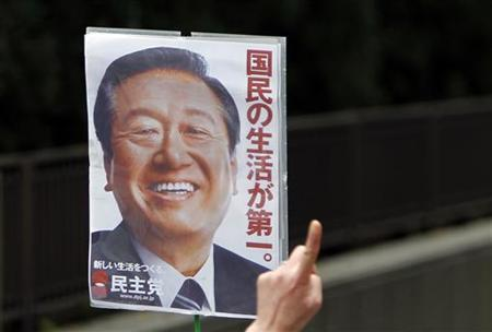 A supporter of Japan's ruling Democratic Party of Japan powerbroker Ichiro Ozawa raises a poster with his image outside the Tokyo District Court in Tokyo April 26, 2012. REUTERS/Toru Hanai