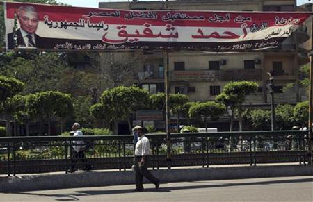 People walk under a banner depicting a picture of former presidential candidate and Egypt's former Prime Minister Ahmed Shafiq in Cairo April 24, 2012. REUTERS/Amr Abdallah Dalsh