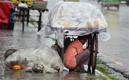 A fruit vendor takes shelter under his cycle-stall during a monsoon shower in New Delhi September 20, 2010. REUTERS/Parivartan Sharma/Files