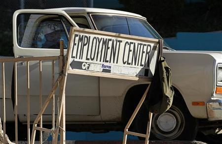 A day laborer sits in a truck behind a sign for an employment center in San Diego, January 6, 2011. REUTERS/Mike Blake