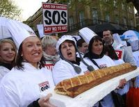 Bakers and their supporters hold a giant sausage roll as they protest opposite Downing Street in central London April 26, 2012. REUTERS/Luke MacGregor