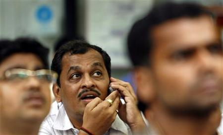 A man speaks on a mobile phone as he looks at a large screen displaying India's benchmark share index on the facade of the Bombay Stock Exchange (BSE) building in Mumbai October 29, 2007. REUTERS/Punit Paranjpe/Files