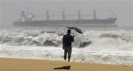 A man holding an umbrella watches large waves on the Marina beach as a cargo ship passes after Cyclone Thane hit the southern Indian state of Tamil Nadu December 30, 2011. REUTERS/Babu