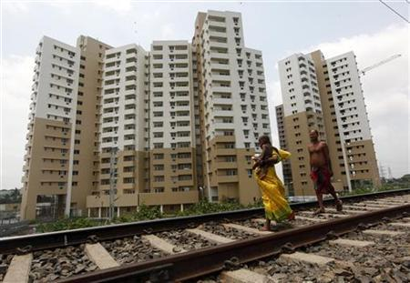 A woman carrying a child walks ahead of her husband on a railway track in front of residential buildings under construction on the outskirts of Kolkata April 26, 2012. REUTERS/Rupak De Chowdhuri
