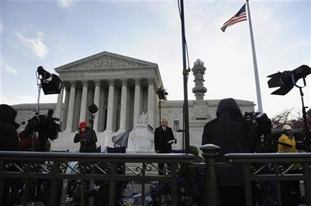Television news networks report live on the sidewalk during the third and final day of legal arguments over the Patient Protection and Affordable Care Act at the Supreme Court in Washington, March 28, 2012. REUTERS/Jonathan Ernst