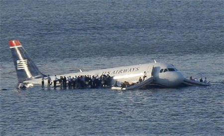 Passengers stand on the wings of a U.S. Airways plane as a ferry pulls up to it after it landed in the Hudson River in New York, January 15, 2009. Local media said the plane was an Airbus with 146 passengers and five crew which had just taken off from La Guardia Airport and was trying to return after apparently striking a flock of birds. REUTERS/Brendan McDermid