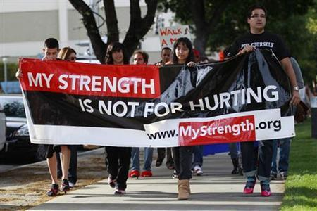 Participants, many wearing women's high heels, carry a sign during the 10th annual Walk A Mile In Her Shoes to raise awareness against sexual violence in Plaza De Cesar Chavez in San Jose, California April 18, 2012. REUTERS/Stephen Lam