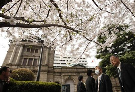 People walk past the Bank of Japan headquarters as cherry blossoms are in full bloom in Tokyo April 10, 2012. REUTERS/Yuriko Nakao