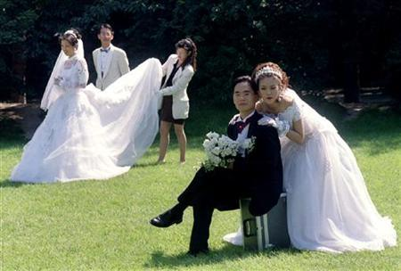 Two South Korean couples pose for their wedding pictures in central Seoul September 12. REUTERS/Paul Barker/Files