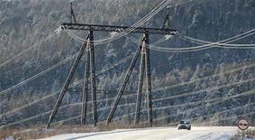 Машина проезжает под ЛЭП, идущей от Красноярской ГЭС 11 ноября 2010 года. Российский энергохолдинг ИнтерРАО увеличил EBITDA в прошлом году на 24,1 процента после консолидации новых активов, оказавшись на уровне прогноза. При этом компания получила операционный убыток. REUTERS/Ilya Naymushin