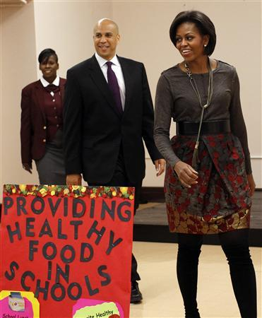U.S. First Lady Michelle Obama walks with Newark New Jersey Mayor Cory Booker (C) and Principal Deneen Washington (L) of the Maple Avenue School during a visit to the school visit to promote her ''Let's Move'' initiative to reduce childhood obesity in this file photo taken in Newark, New Jersey on November 18, 2010. REUTERS/Mike Segar/Files