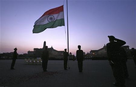 Soldiers are silhouetted against the setting sun as they salute facing the national flag in New Delhi January 24, 2012. REUTERS/Parivartan Sharma