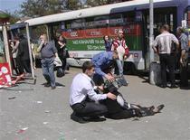"""Люди помогают раненой женщине на месте взрыва в Днепропетровске 27 апреля 2012 года. Украинский президент Виктор Янукович назвал """"вызовом"""" для страны и пообещал """"достойный"""" ответ на ранившие почти десятка человек четыре взрыва, прогремевшие в течение часа в пятницу, почти за месяц до чемпионата Европы по футболу, который впервые примет Украина. REUTERS/Stringer"""