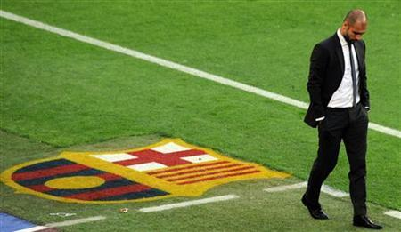 Barcelona's coach Pep Guardiola walks in the sideline during their Spanish first division ''El Clasico'' soccer match against Real Madrid at Nou Camp stadium in Barcelona April 21, 2012. REUTERS/Sergio Carmona