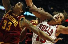Chicago Bulls' Joakim Noah (R) is hit with an elbow as he goes for a rebound against Cleveland Cavaliers' Alonzo Gee during the second half of their NBA basketball game in Chicago, April 26, 2012. REUTERS/Jim Young