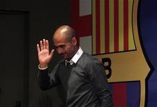 Técnico do Barcelona Pep Guardiola acena ao final da coletiva de imprensa no estádio Camp Nou, em Barcelona. Guardiola vai deixar o time catalão no final da temporada e será substituído por seu assistente Tito Vilanova. 27/04/2012 REUTERS/Albert Gea
