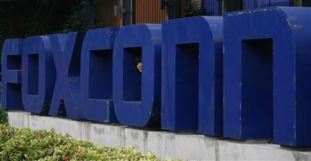 A Foxconn worker looks out from the company logo outside a Foxconn factory in the township of Longhua in the southern Guangdong province May 27, 2010. REUTERS/Bobby Yip