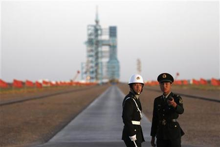 Soldiers stand in front of the Long March II-F rocket loaded with China's unmanned space module Tiangong-1 before its planned launch from the Jiuquan Satellite Launch Center, Gansu province September 29, 2011. REUTERS/Petar Kujundzic