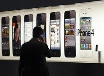Homem fala em iPhone em frente a um anúncio na loja da Apple em Hong Kong, em setembro de 2011. Apple provavelmente verá alta de quase 100 por cento em seu crescimento no mercado chinês este ano. Foto de arquivo 21/09/2011 REUTERS/Tyrone Siu/Arquivo