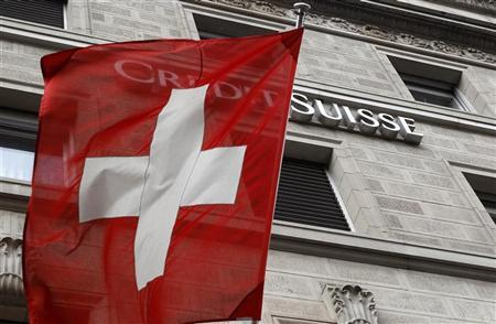 A Switzerland national flag flies in front of the logo of Swiss bank Credit Suisse (CS) at a branch office in Zurich April 13, 2012. REUTERS/Arnd Wiegmann