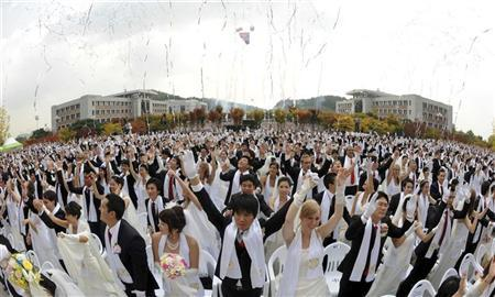 Newlyweds give three cheers during a mass wedding ceremony at Sun Moon University in Asan, south of Seoul October 14, 2009. REUTERS/Segye Times /Handout