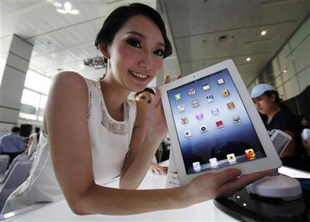 A model poses with a third generation iPad at a shop in Bangkok April 27, 2012. REUTERS/Chaiwat Subprasom/Files