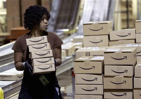 A worker loads a shipment of outgoing boxes at the Amazon.com warehouse facility in New Castle, Delaware in this November 24, 2006 file photo. REUTERS/Tim Shaffer/Files