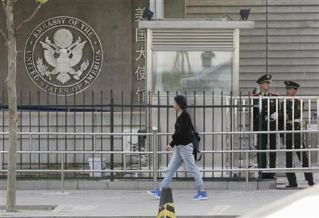 A woman walks past paramilitary police officers standing guard outside the U.S. embassy in Beijing April 28, 2012. Blind Chinese activist Chen Guangcheng is under U.S. protection in Beijing after an audacious escape from 19 months under house arrest, a U.S.-based group said on Saturday. REUTERS/Jason Lee