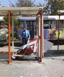 Полицейский на разрушенной взрывом трамвайной остановке в Днепропетровске 27 апреля 2012. Украинские власти и оппозиция обменялись взаимными обвинениями в попытке установить, кому из политиков выгодна потрясшая Днепропетровск серия взрывов, чудом обошедшихся без жертв. REUTERS/Stringer