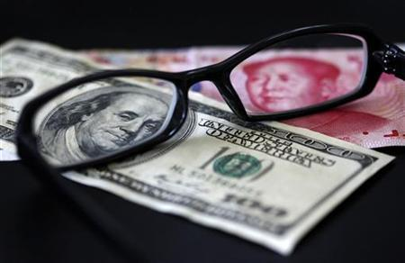 A U.S. dollar note (L) and a Chinese yuan banknote are seen through a pair of spectacles in this picture illustration taken in Taipei October 13, 2010. REUTERS/Nicky Loh/Files