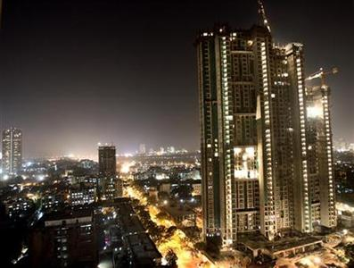 A high-rise building is lit up during construction in Mumbai December 22, 2006. REUTERS/Arko Datta/Files