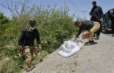 Police survey the site where the body of Khalil Rasjed Dale, a British doctor working with the International Committee of the Red Cross, was found at a roadside in Quetta April 29, 2012. The beheaded body of the kidnapped British doctor was found dumped by the roadside on Sunday in the southwestern Pakistan city of Quetta, police and Red Cross officials said. Dale, 60, was kidnapped by suspected militants on Jan 5 while on his way home from work. REUTERS/Naseer Ahmed