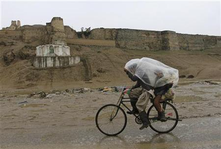 Afghan boys ride a bicycle under a plastic sheet during a rainy day in Kabul April 19, 2012. REUTERS/Mohammad Ismail