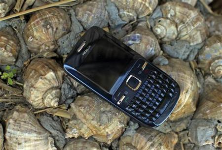 A Nokia phone is seen on a bed of shells in the Black Sea resort of Mamaia, about 260km (162 miles) east of Bucharest April 29, 2012. REUTERS/Radu Sigheti