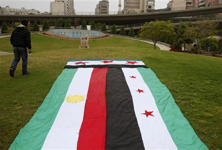 A Syrian Kurd walks past giant Kurdish (L) and Syrian opposition flags ahead of a sit-in in front of the United Nations headquarters in Beirut, in solidarity with anti-government protesters in Syria, April 29, 2012. REUTERS/Cynthia Karam
