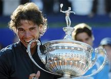 O espanhol Rafael Nadal morde o troféu Conde de Godo após derrotar seu compatriota David Ferrer e vencer o torneio de tênis Barcelona Open, em Barcelona, 29 de abril de 2012. REUTERS/Albert Gea