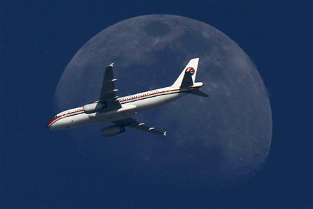 A China Eastern Airlines passenger jet passes in front of the moon over Shanghai in this May 13, 2011 file photograph. REUTERS/Aly Song/Files