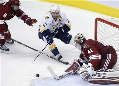 Phoenix Coyotes goalie Mike Smith (41) makes a 3rd period save on Nashville Predators center Mike Fisher (12) during Game 2 of the NHL Western Conference semi-final hockey playoffs in Phoenix, Arizona, April 29, 2012. REUTERS/Darryl Webb