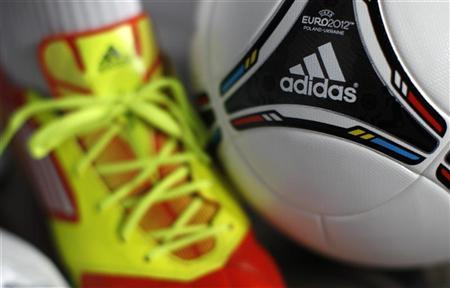 A shoe and a soccer ball by German sporting goods maker Adidas are pictured before the company's annual news conference in the northern Bavarian town of Herzogenaurach March 7, 2012. REUTERS/Michaela Rehle (GERMANY - Tags: BUSINESS)